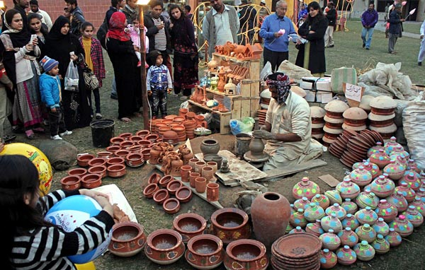 Px22-057 LAHORE: Feb22 - People taking interest in the items displayed on a stall during Jashn-e-Baharan Festival at Race Course, Jilani Park. ONLINE PHOTO by Sajid Rana