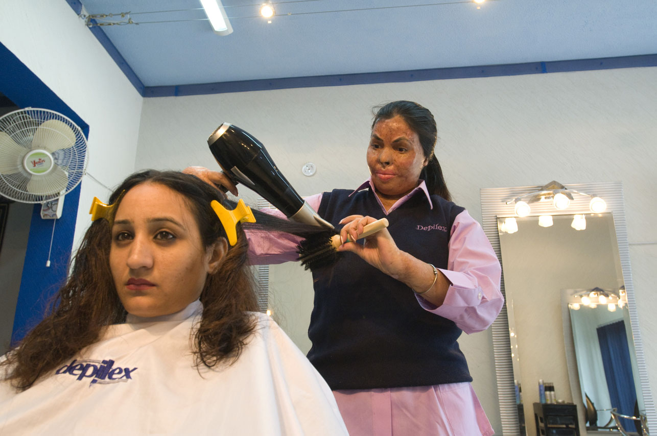 Sabira Manzoor, 31 year old burn victim, (right) working with client, Bushra, at the Depilex salon in Islamabad, Pakistan on November 17, 2008. Sabira was burned 15 years ago by her husband who lit her on fire with kerosine oil. After 30 surgeries, Sabira is doing a lot better and is presently working at the Smile Again beauty salon in Lahore and the Depilex Salon in Islamabad Pakistan as a beautician.
